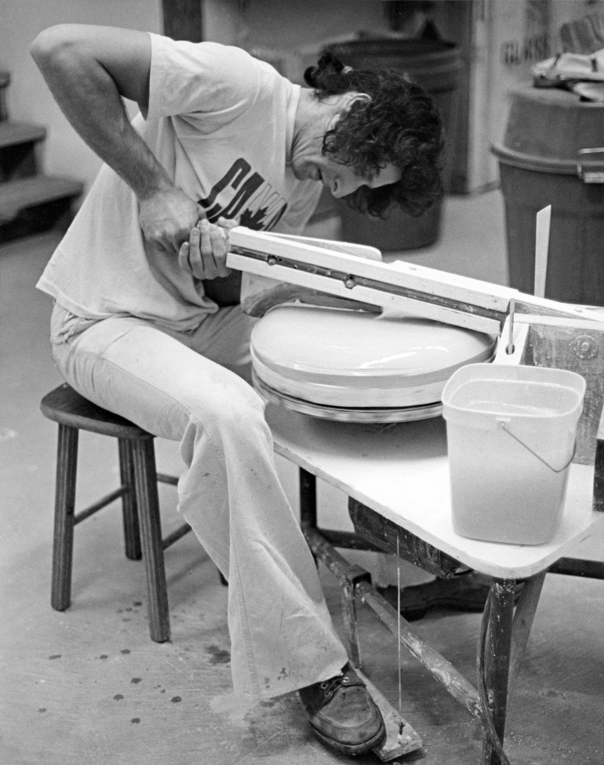Leonard Skuro jiggering a plate in the ceramics studio, Santa Monica, CA, c. 1976-1977