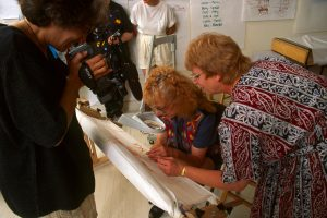 Judy Chicago tries her hand at stitching the Needlework Sampler in Belen, NM 1997